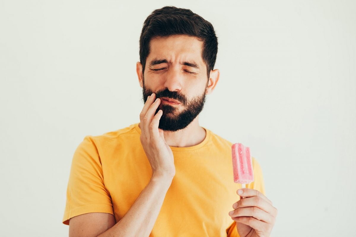Man with sensitive teeth eating ice cream.