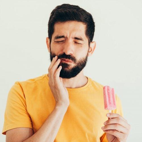 Man with sensitive teeth eating ice cream.