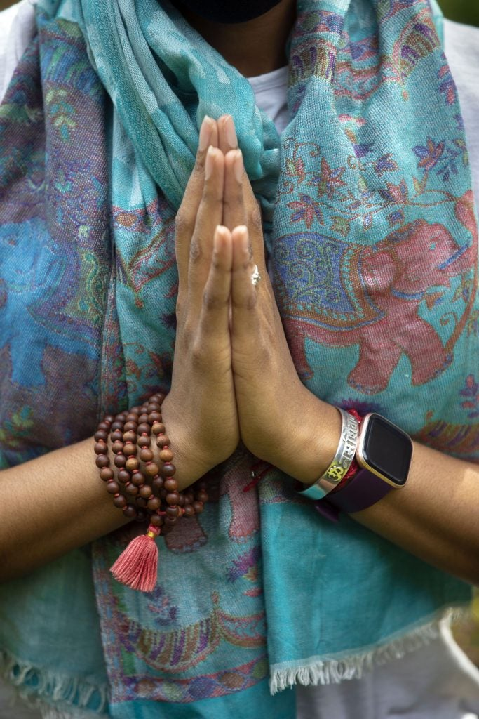 Jessica Chang practices yoga, holding her hands in a prayer.
