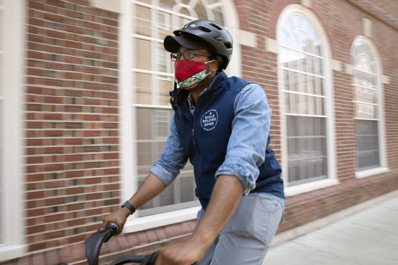 Darold Cuba, Harvard Kennedy School Mid career MPA rides a blue bike near Leverett House.