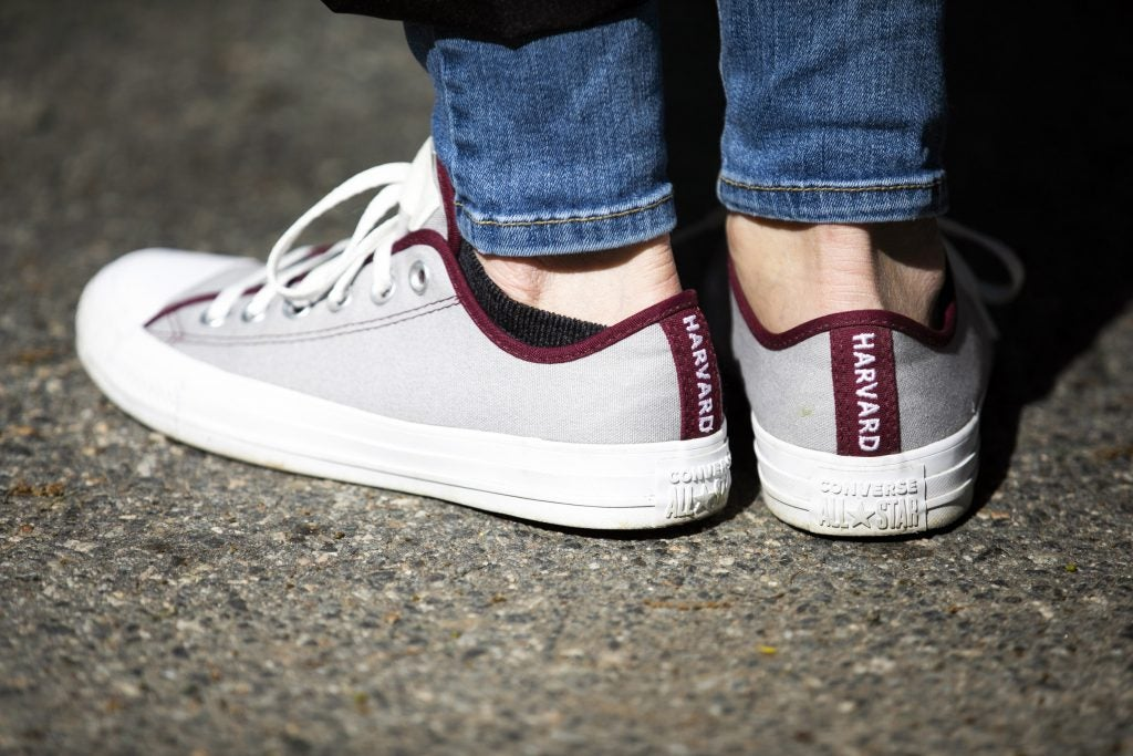 Converse sneakers that read Harvard along the back.