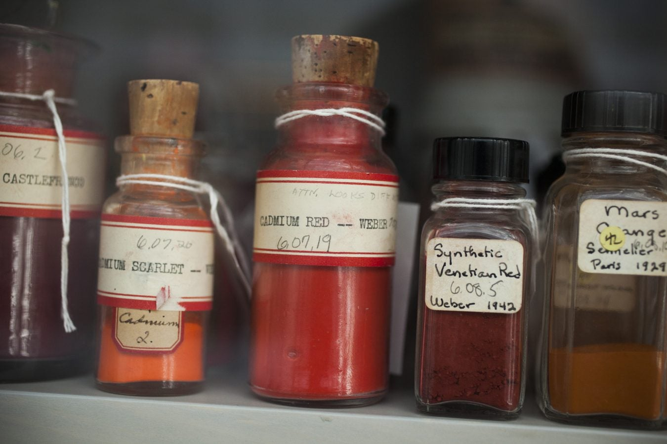 a collection of pigments in glass jars.