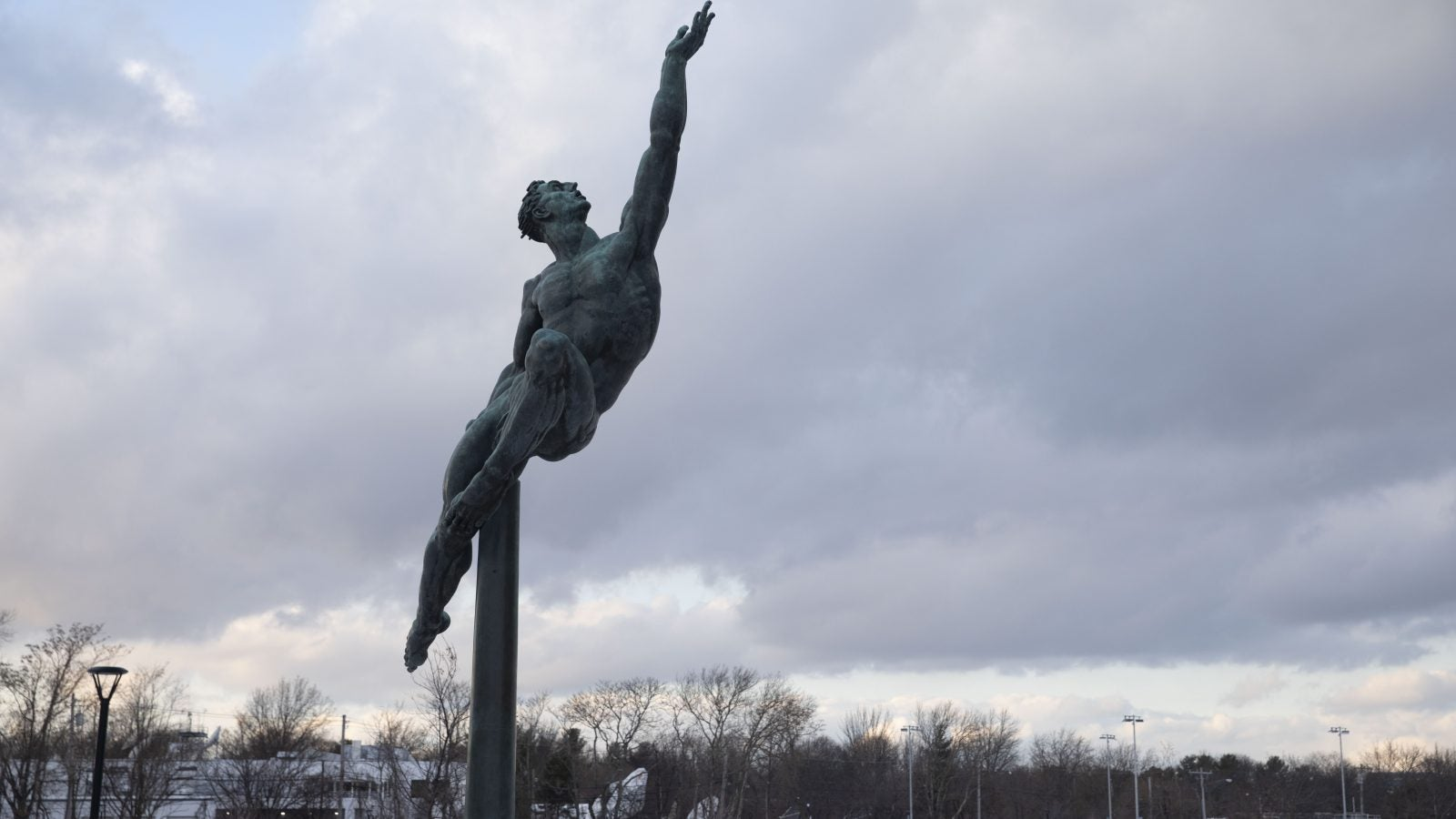A statue of someone leaping and reaching to the heavens.