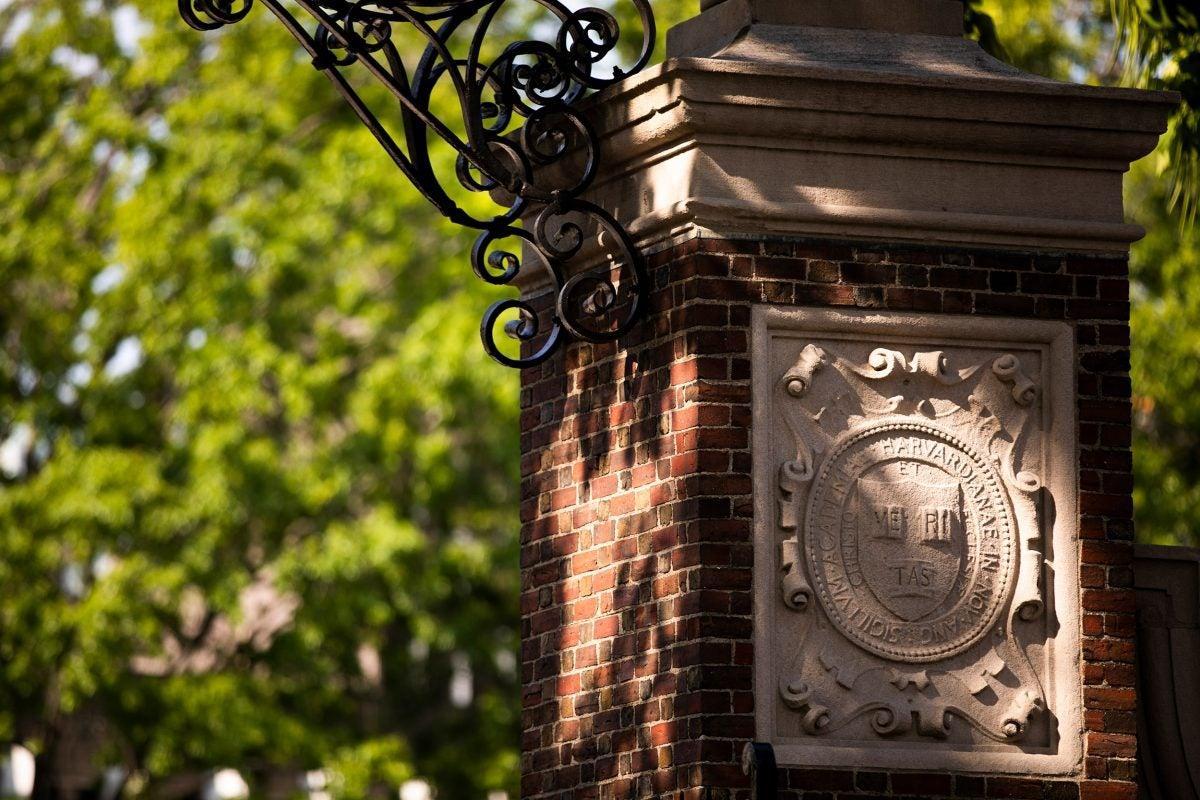 A veritas shield decorates a Harvard Yard gate.