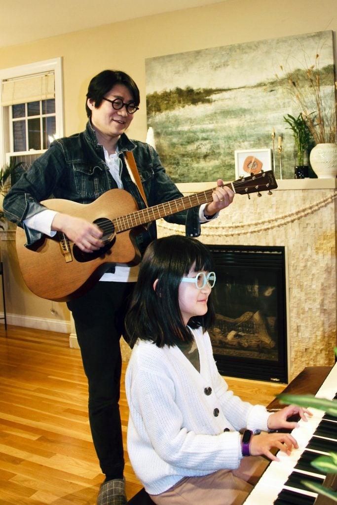 Yuha Wang playing music with his daughter.
