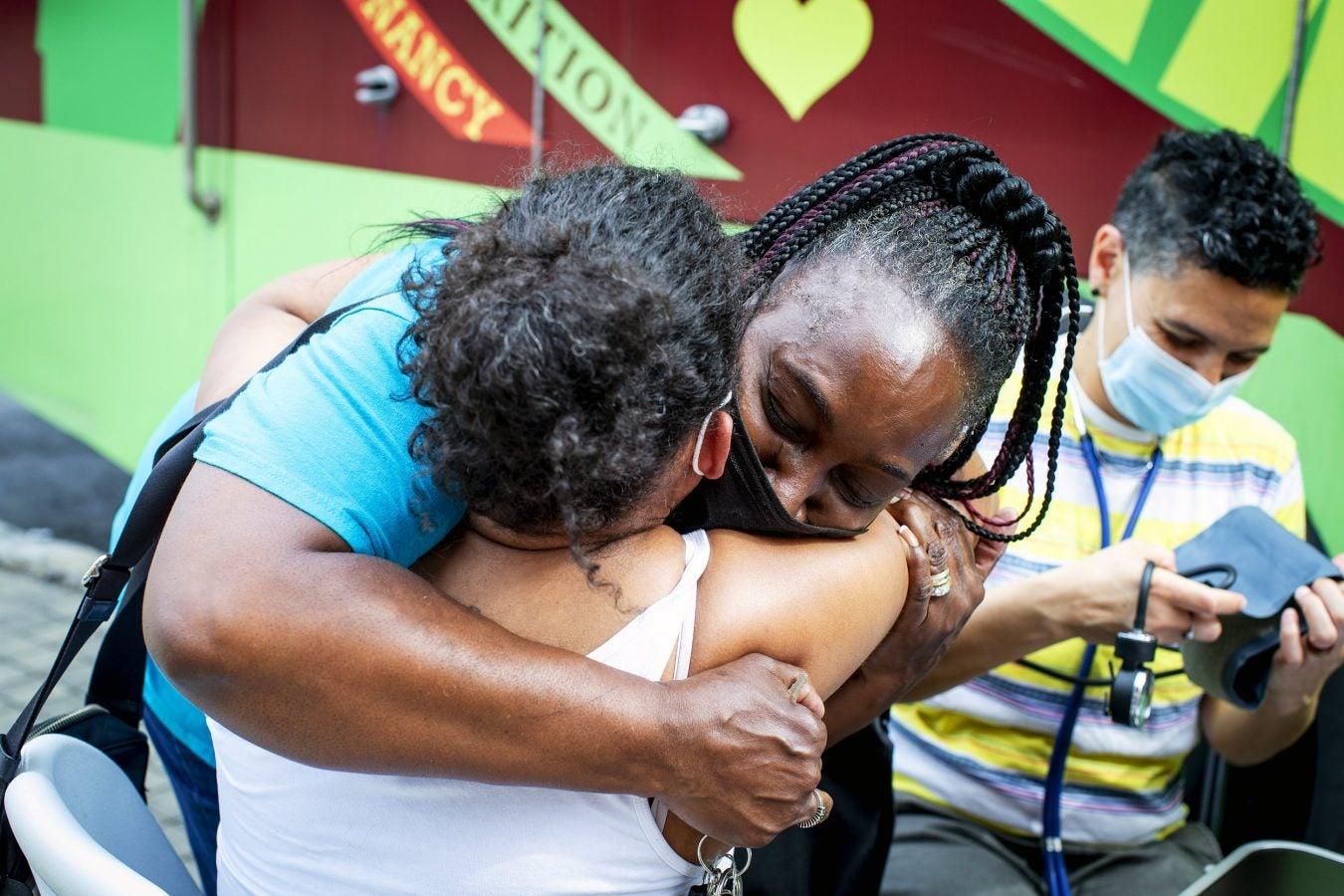 Assistant Director, Rainelle Walker White (facing camera) heartily greets fellow staffer, Joanne Suarez at Harvard University's Family Van.