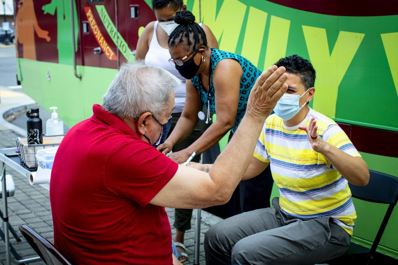 Simone de Oliveira, right, high fives a regular client, Joseph Rocca, of Winthrop, after administering his blood pressure test.