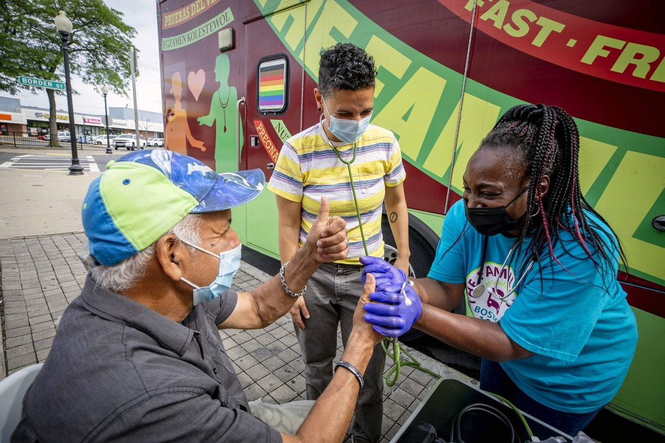 Simone de Oliveira, center and Rainelle Walker White, right, assistant director, work together to administer a blood pressure test to Wilson Viana Silva of E. Boston at Harvard University's Family Van.