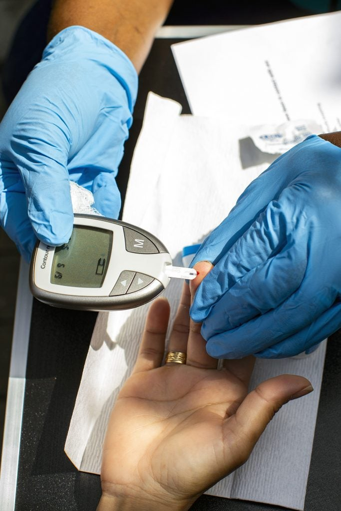 A member of the Family Van staff administers a blood sugar test.