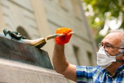 Robert Shure restoring John Harvard Statue.