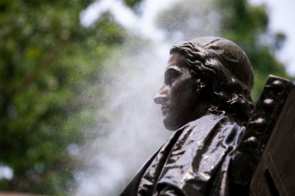 John Harvard statue being cleaned.
