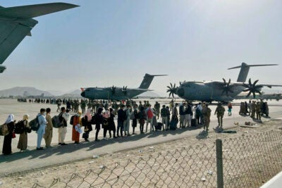 Afghan people wait at Kabul's airport.