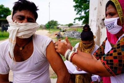India worker giving vaccines door to door.