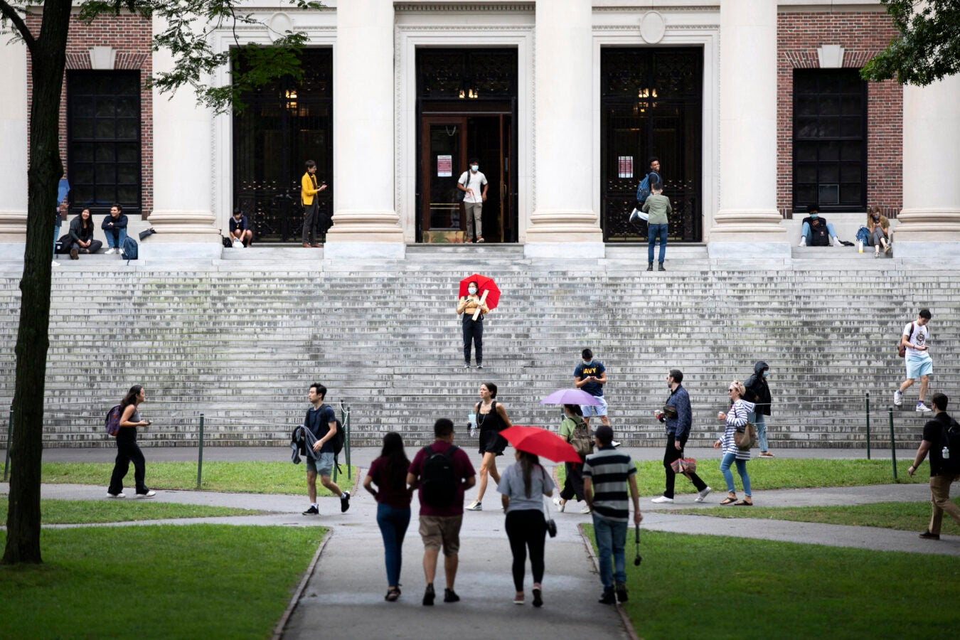 People parade by the steps of Widener Library.