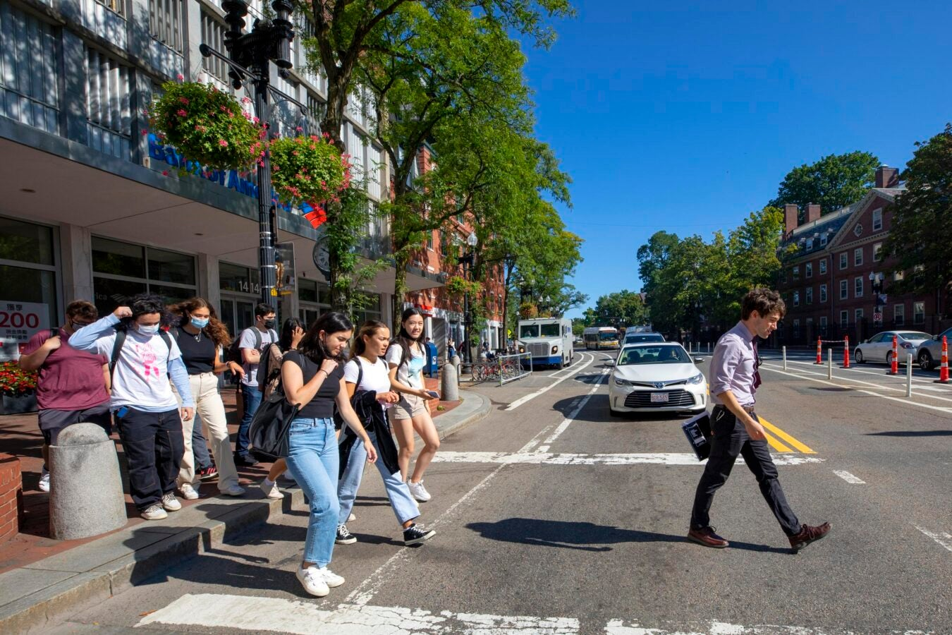 William Whitham walks with his students across Massachusetts Avenue.
