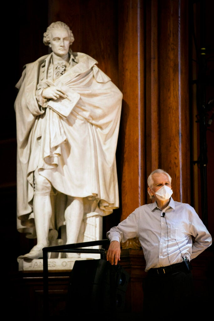 Charles Czeisler stands by the statue in Sanders Theatre during his lecture on Sleep.