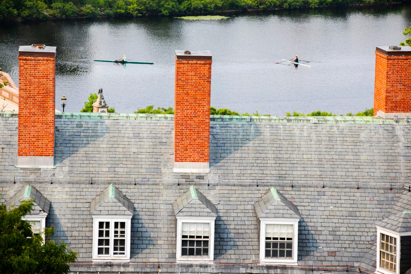 The chimneys of Eliot House frame rowers along the Charles River.