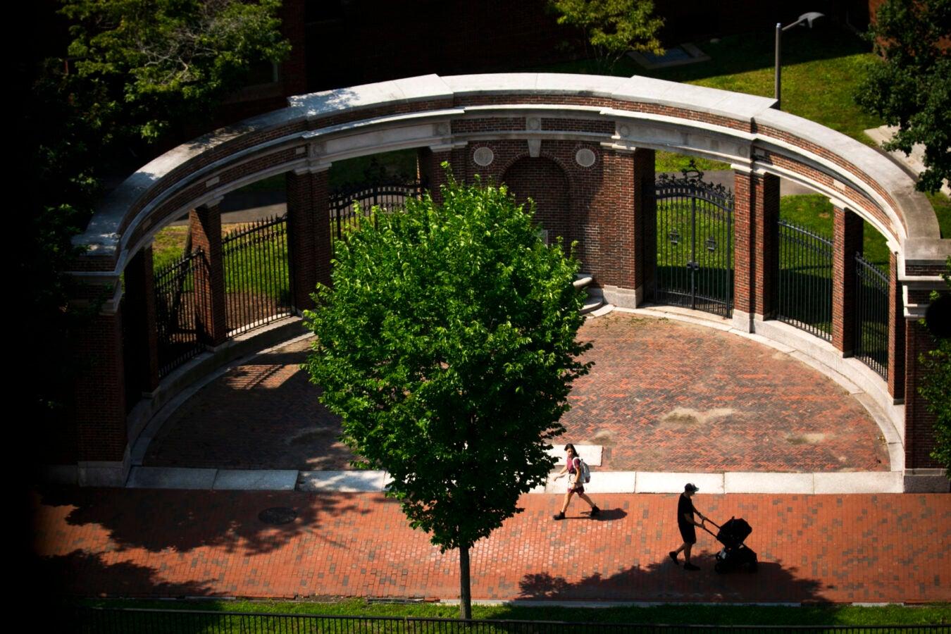 Pedestrians pass alongside the gates of Harvard Yard.