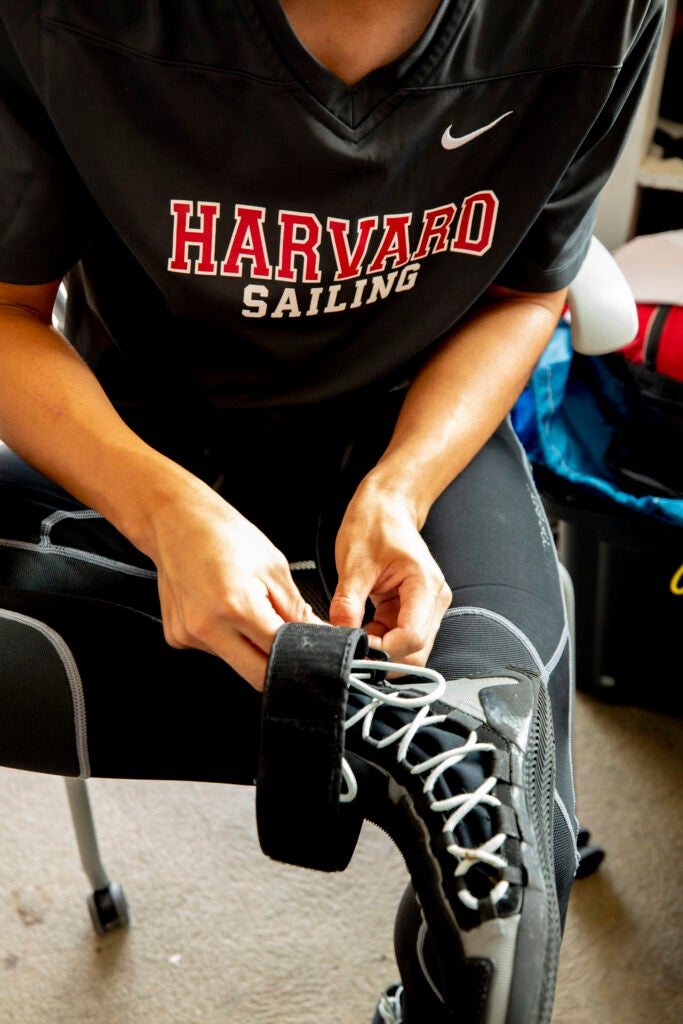 A sailor puts on his boot (possibly minus his sock).