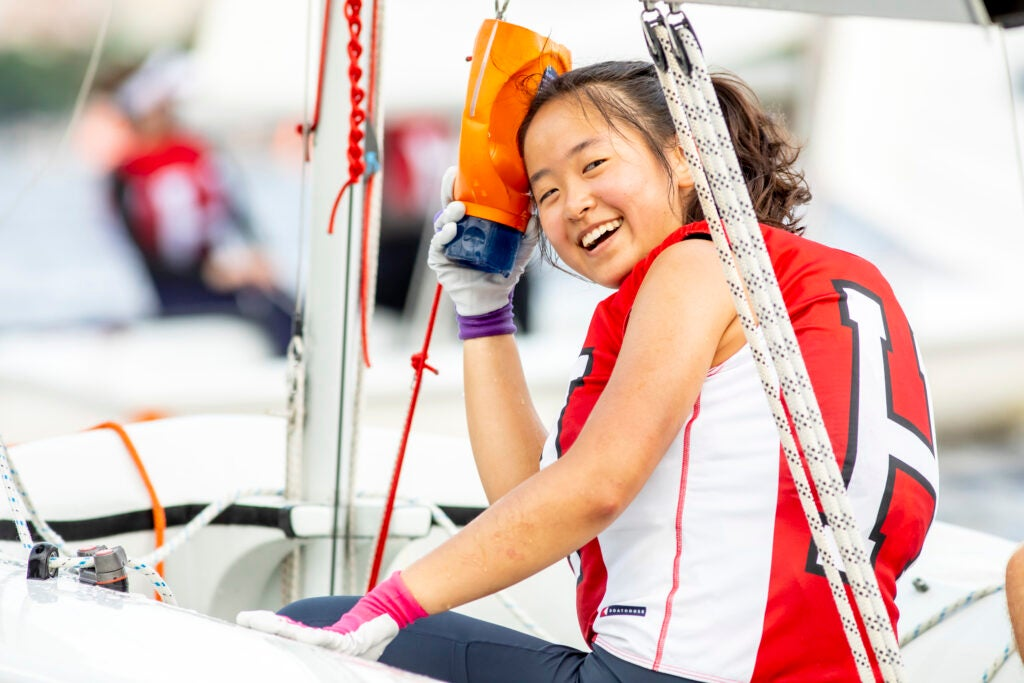 Carolyn Wang manages a smile after hitting her head on the boom. She ices the sore spot with the baler.