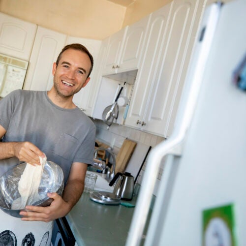 Lucas Harty mixes his sourdough and sourdough started during Covid in his Central Square apartment.