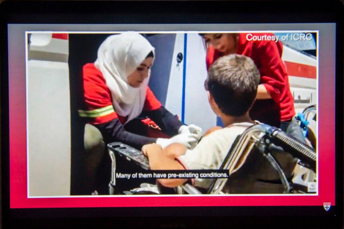 Red Cross worker helping boy.
